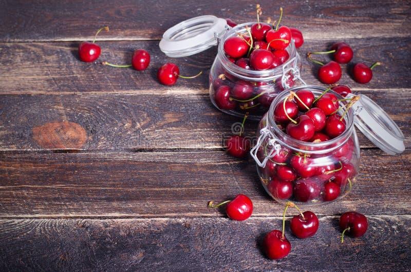 Cerises rouges dans un pot en verre sur le fond en bois foncé avec l'espace de copie Été et concept ensoleillés de récolte Cherry image libre de droits