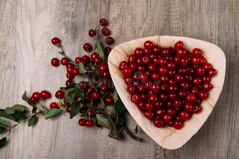 Cerises rouges fraîches dans un plat en bois sur une table en bois Plat en bois sur un fond en bois à côté de elle est une branch photo stock