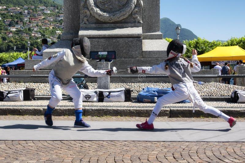 CERNOBBIO, ITALIË - JUNI 16, 2019: Jong geitjeschermers die en met zwaard schermen praktizeren royalty-vrije stock fotografie