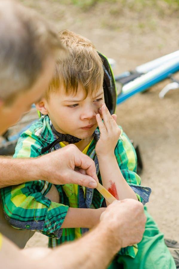 Cerotto mettente di prima generazione sulla lesione del giovane ragazzo che ha cad da dalla sua bicicletta fotografia stock