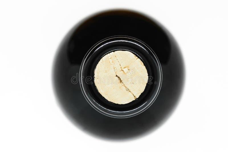 Cerrado con la opinión de cristal negra de botella de vino del corcho del top en el fondo blanco fotos de archivo