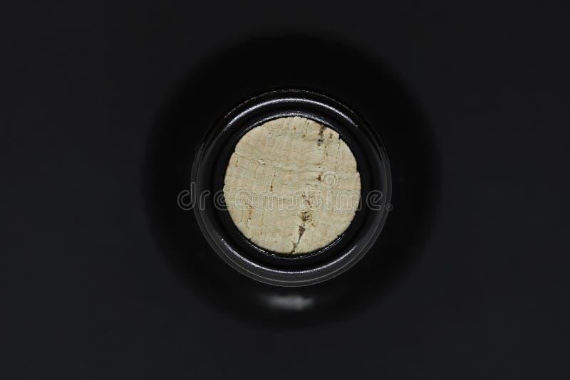 Cerrado con la opinión de cristal negra de botella de vino del corcho del top en fondo negro fotografía de archivo