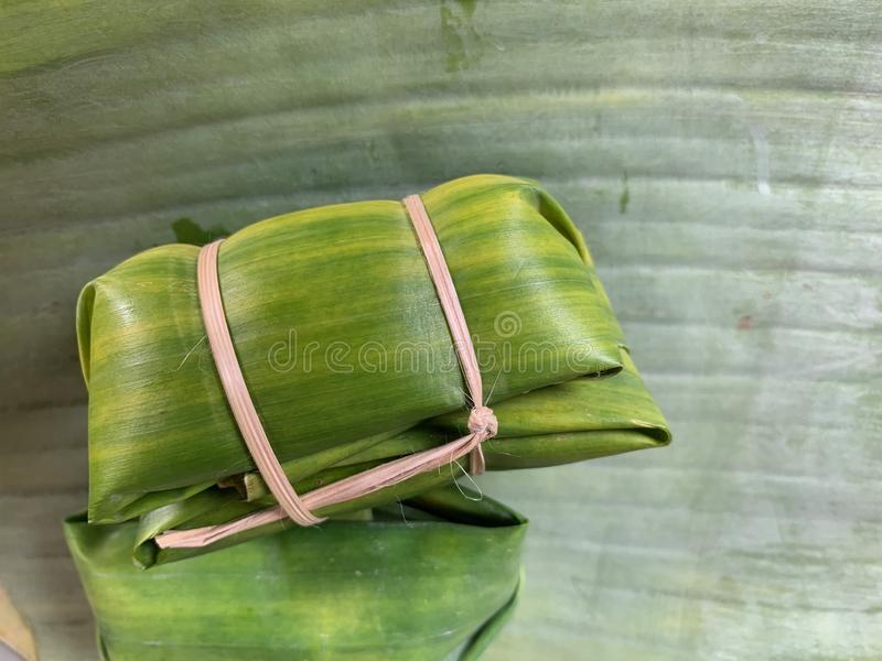 Cerrado encima de la imagen de las gachas de avena del arroz, de los plátanos con arroz pegajoso en las hojas verdes del plátano  fotos de archivo