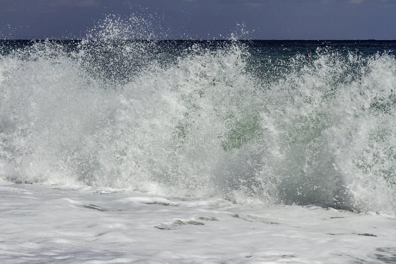 Cerrado encima de la inflamación majestuosa de la turquesa que se estrella en la playa en un día de verano del cielo azul en Sici imágenes de archivo libres de regalías