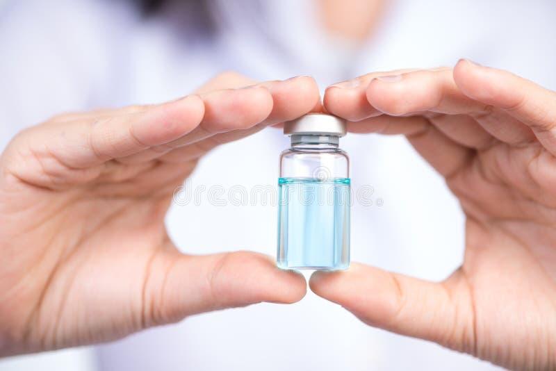 Cerrado encima de la mano del frasco de la inyección del control de la enfermera imagen de archivo libre de regalías
