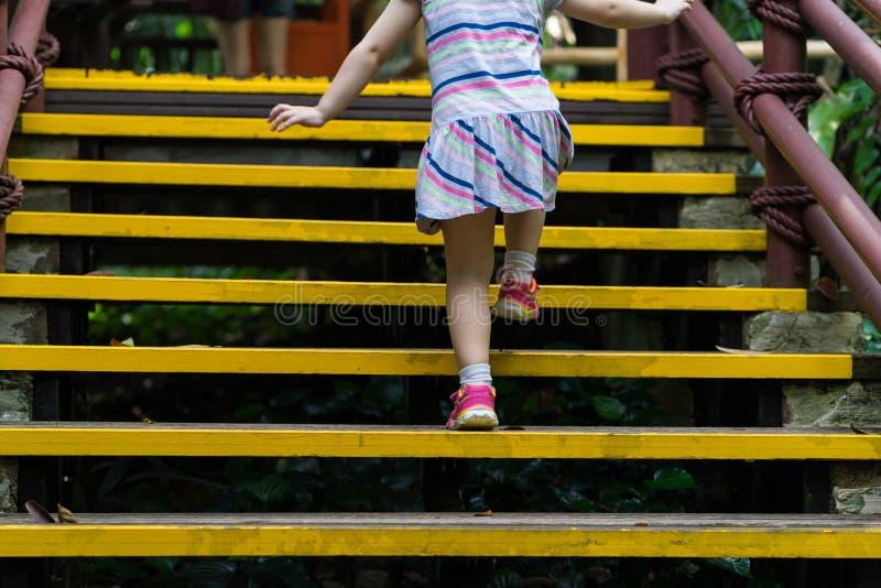 Cerrado encima de la niña que sube para arriba las escaleras al aire libre foto de archivo libre de regalías