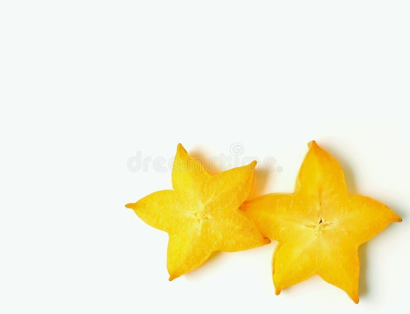 Cerrado encima de pares de amarillo vibrante cortó las frutas de estrella maduras en el fondo blanco, con el espacio libre para e imágenes de archivo libres de regalías