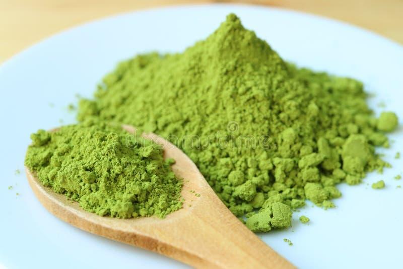 Cerrado encima de una cuchara del polvo verde vibrante del té de Matcha en una placa con la pila borrosa del polvo del té verde e imagen de archivo