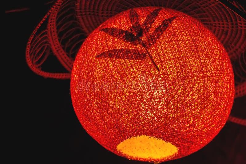 Cerrado encima del color rojo de la linterna de papel del terciopelo y de la hoja del bambú imagen de archivo