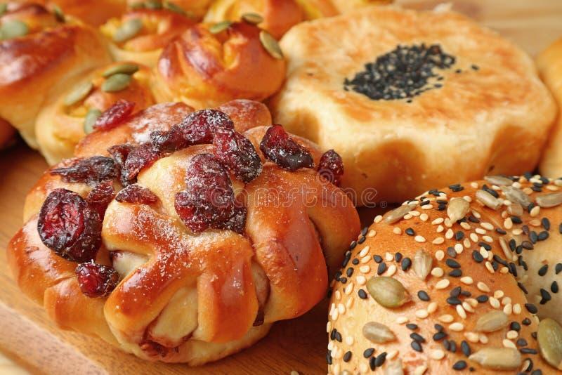 Cerrado encima del pan con las frutas secadas y otros diversos tipos de panes hechos frescos servidos en la bandeja de madera imagen de archivo libre de regalías