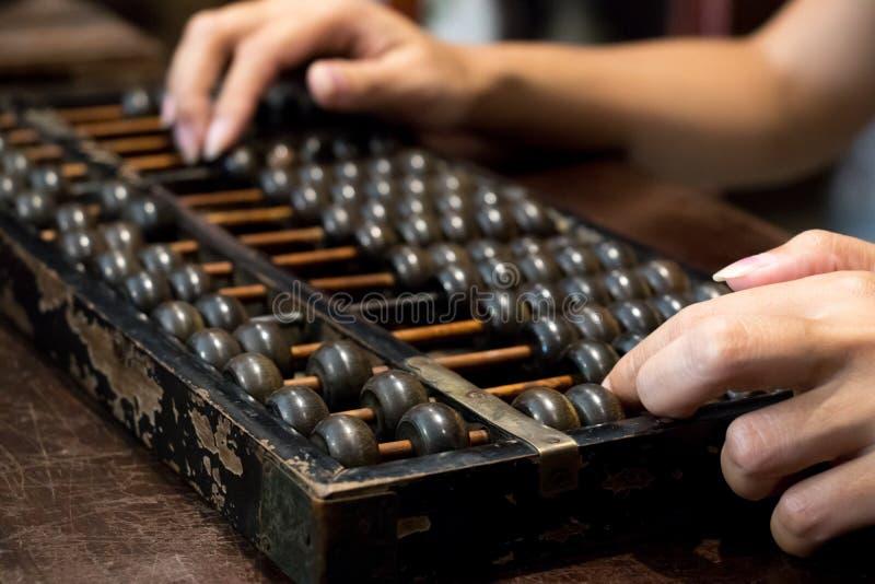 Cerrado para arriba de la mano de la mujer de negocios que calcula con el ábaco de madera fotos de archivo
