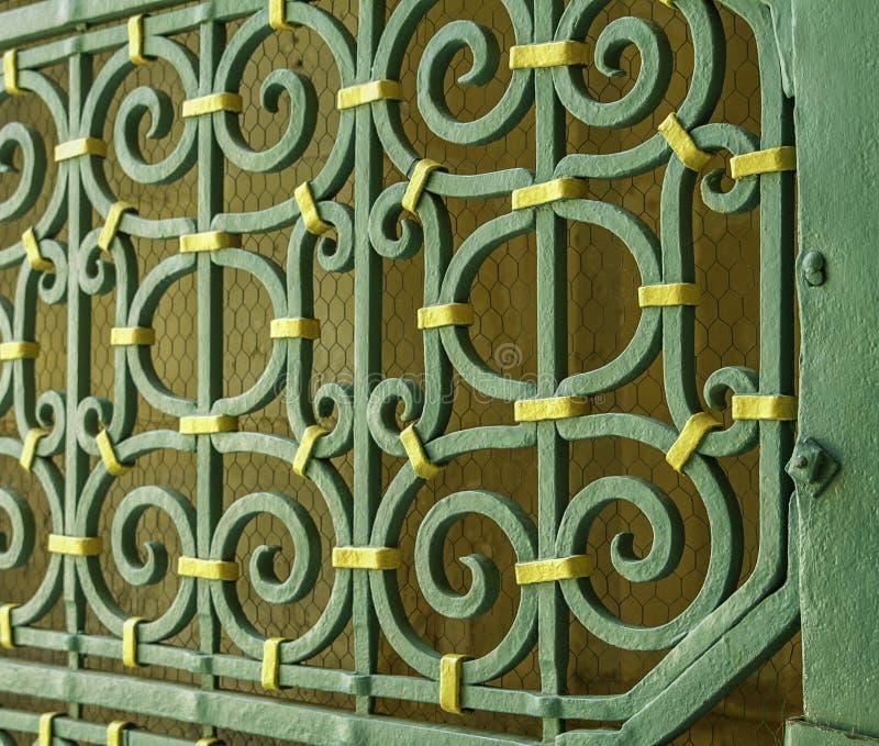 Cerrado para arriba de verde histórico externo de la iglesia y de la puerta adornada amarilla del metal en Sicilia imagen de archivo