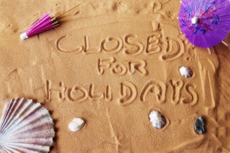 Cerrado por los días de fiesta escritos en la arena imagen de archivo libre de regalías
