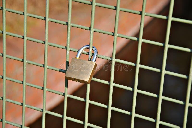Cerradura de seguridad de oro en la cerca fotos de archivo