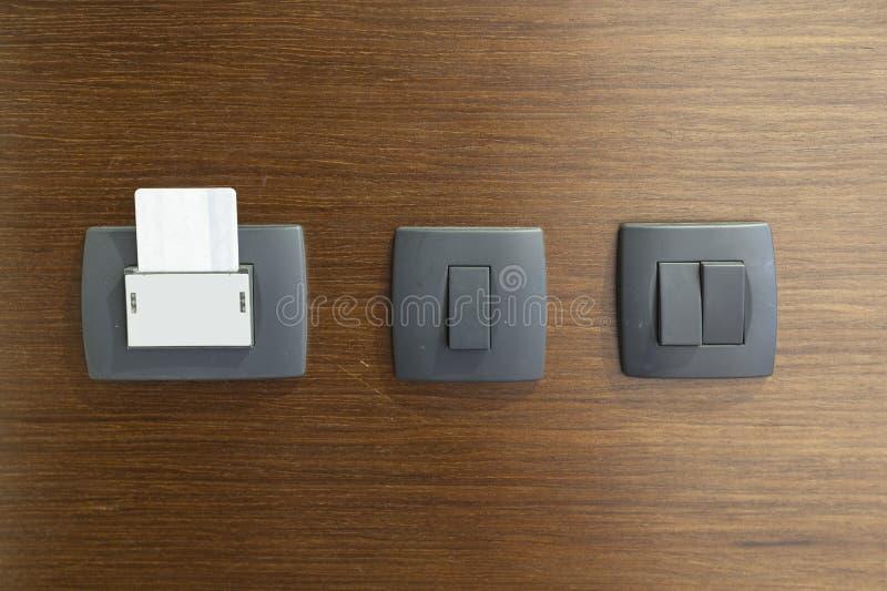 Cerradura electrónica con la tarjeta insertada y interruptores de la luz en la pared de madera en la habitación foto de archivo libre de regalías