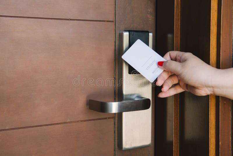 Cerradura electrónica de la habitación de la abertura de la mujer joven con la llave electrónica imágenes de archivo libres de regalías
