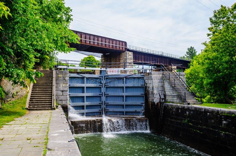 Cerradura en canal con el puente ferroviario que pasa arriba, cerca de Kingston, Ontario, Canadá imagenes de archivo