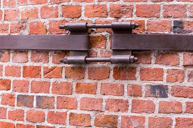 Cerradura oxidada de sujeción de la pared agrietada del fondo industrial la vieja para los tubos sujetó la pared de ladrillo ro foto de archivo libre de regalías
