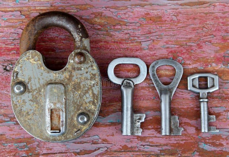 Cerradura oxidada vieja con tres diversas llaves en superficie de madera fotos de archivo libres de regalías