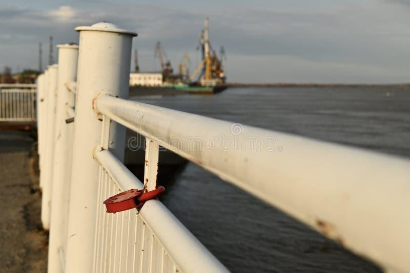 Cerradura roja del metal en la forma de un corazón, colgando en una verja blanca levemente oxidada Contra el contexto del puerto  foto de archivo