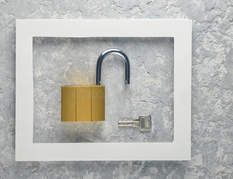 Cerradura y llaves en un marco blanco en un fondo concreto gris Tendencia minimalista imagen de archivo libre de regalías