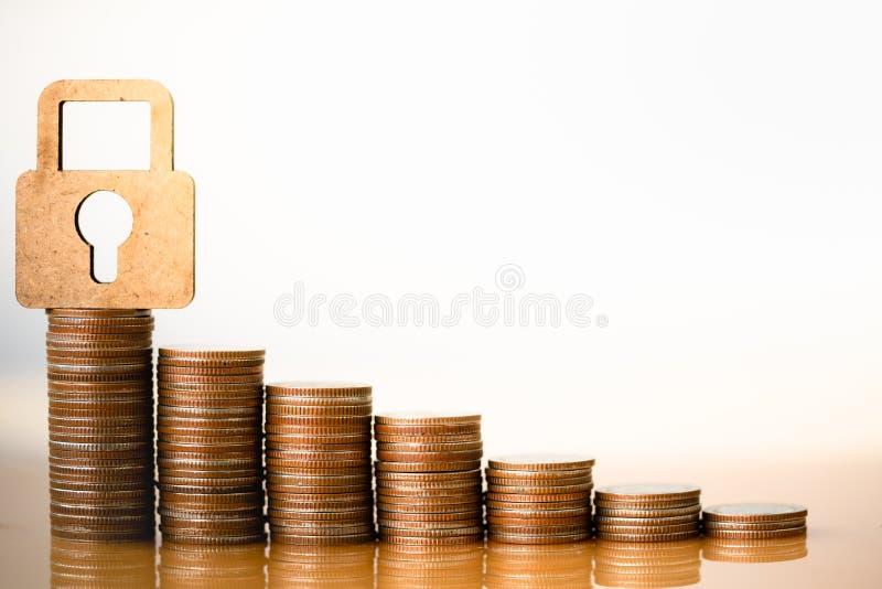 Cerradura y pila de madera de monedas en el concepto de ahorros fotografía de archivo