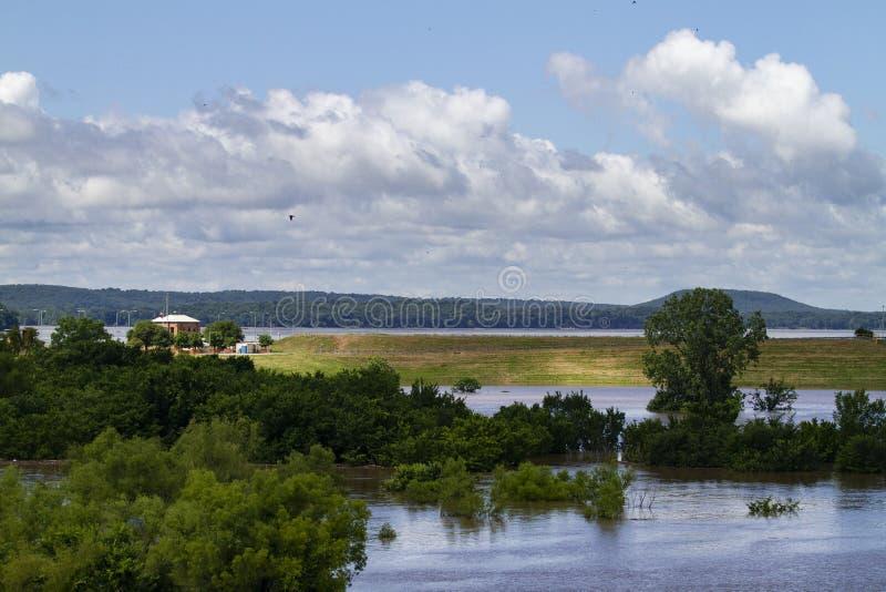 Cerradura y presa de Roberto S Kerr Reservoir durante la inundaci?n, ?rboles en los caudales de una crecida, aliviadero en la dis imagenes de archivo