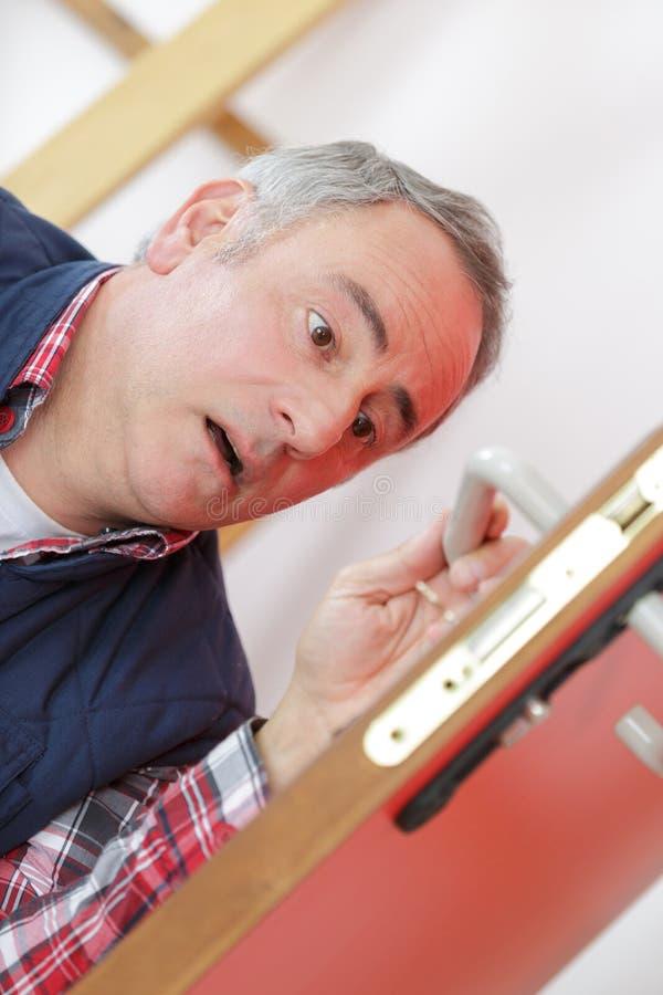 Cerrajero que comprueba la cerradura de puerta foto de archivo libre de regalías