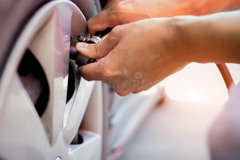 Cerrar la mano del neumático inflado del hombre fotografía de archivo
