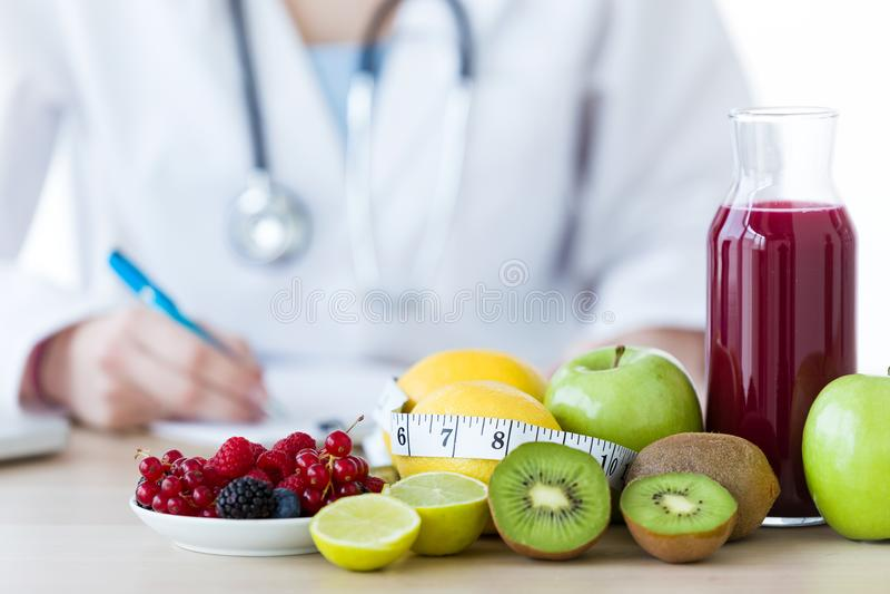Certains fruits tels que des pommes, des kiwis, des citrons et des baies sur la table de nutritionniste photographie stock libre de droits