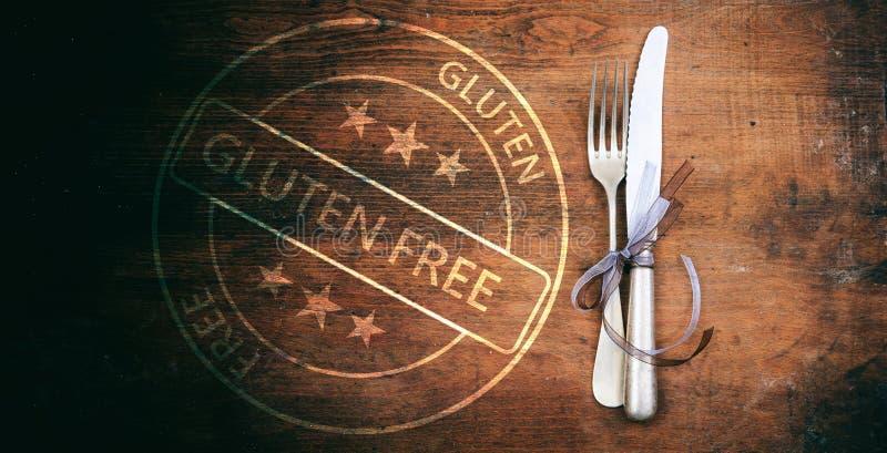 certificación Gluten-libre Sello y cubiertos en la tabla de madera rústica, visión superior imágenes de archivo libres de regalías