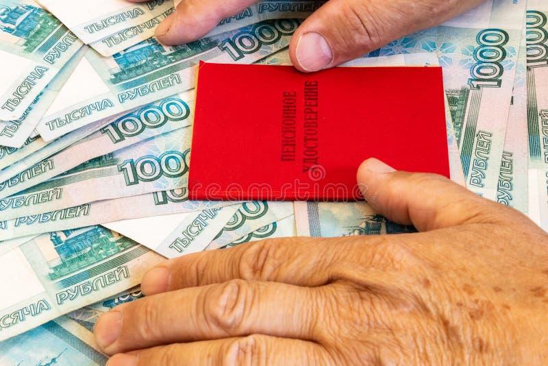 certificado da pensão e pensioner& x27; as mãos de s estão nas contas em 1000 rublos A inscrição no certificado: & x27; pensão fotos de stock