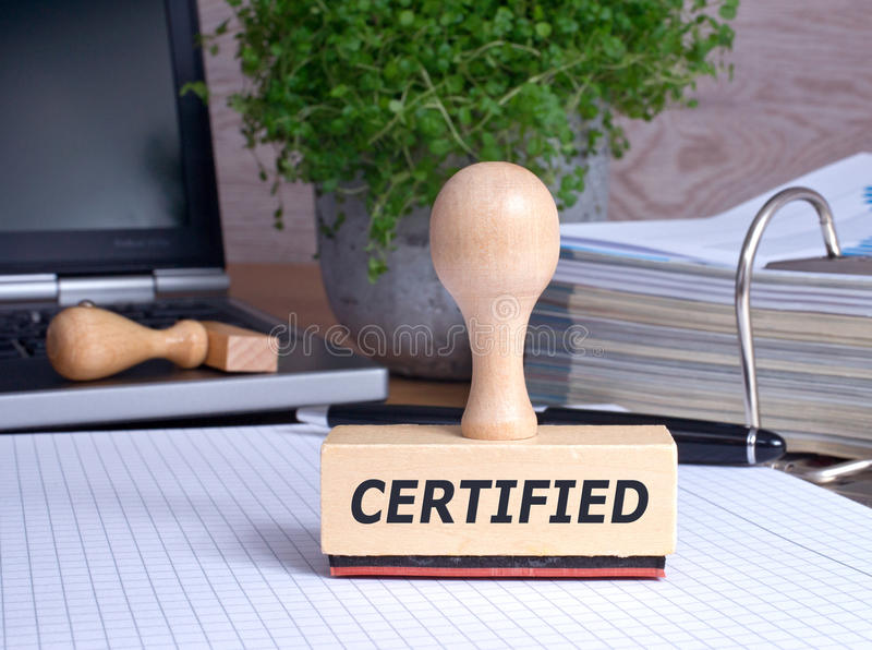 Certified. In black text on wooden rubber stamp on office desk with computer laptop and binder of papers stock photo