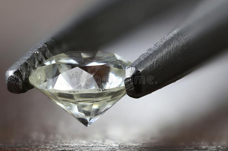 Diamond. Certified 0.45 ct brilliant cut diamond with laser inscription held by tweezers stock images