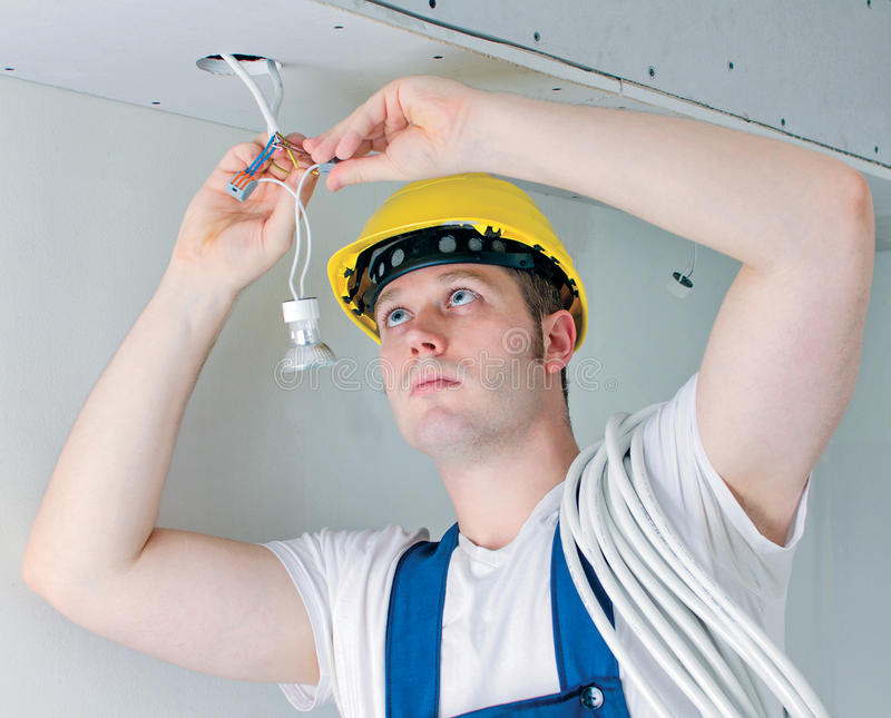 Certified electrician. Installing socket for light bulb royalty free stock image