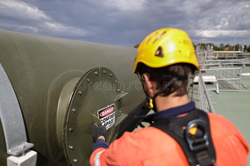 Certifier maintenance construction worker wearing black safety glove full body harness inspection confined space manhole pri stock photos