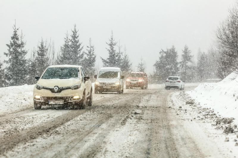 Certovica, Slovakia - Jauary 08, 2019: Cars driving on slippery snow covered forest road during winter blizzard. Drive royalty free stock images