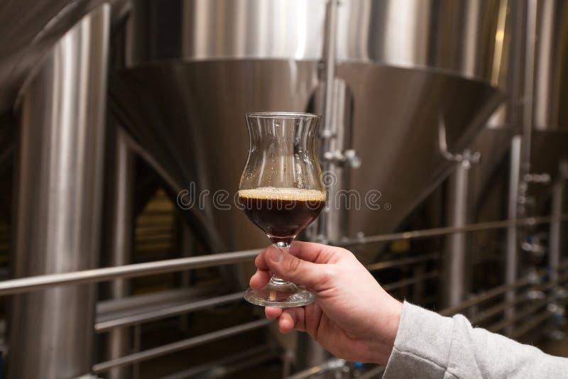 Cervecero de la mano con la cerveza oscura recientemente elaborada foto de archivo