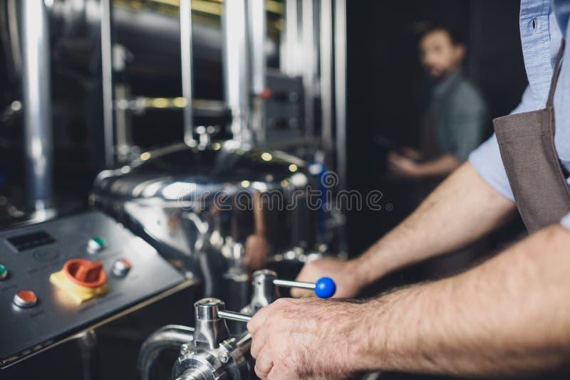 Cervecero que trabaja con el equipo industrial fotografía de archivo libre de regalías