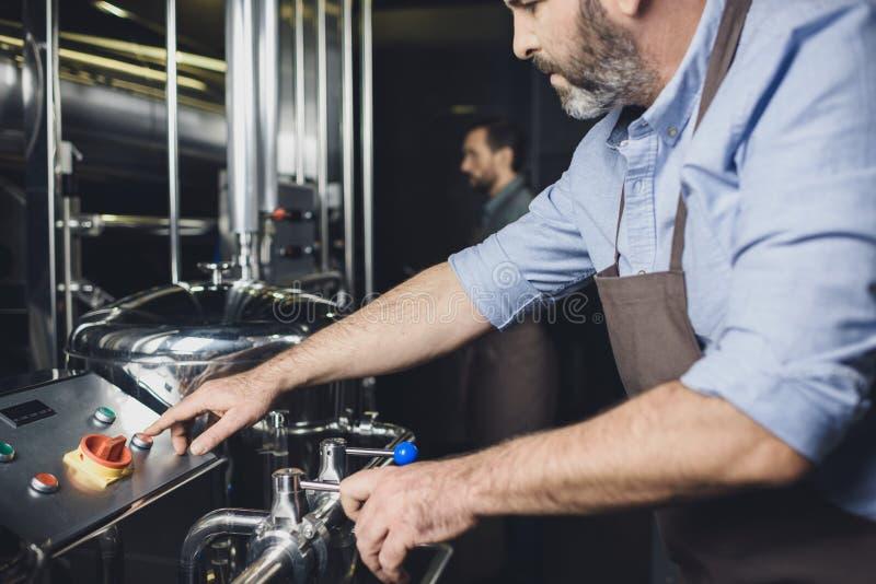 Cervecero que trabaja con el equipo industrial imagenes de archivo