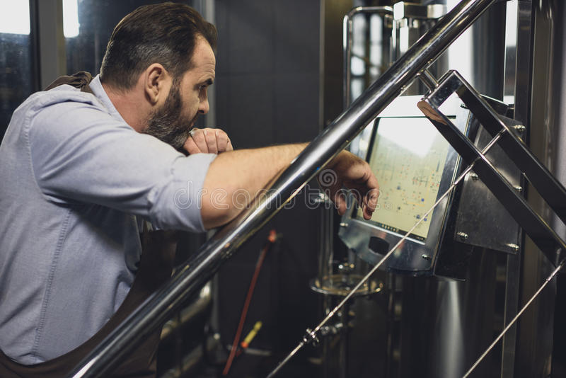 Cervecero que trabaja con el equipo tecnológico fotos de archivo libres de regalías