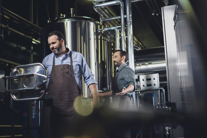 Cerveceros que trabajan con el equipo industrial fotografía de archivo libre de regalías