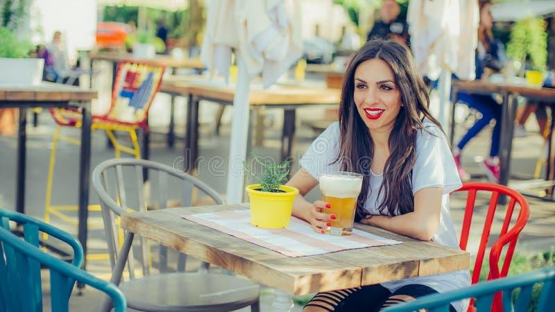 Cerveja bebendo da jovem mulher bonita e apreciação do dia de verão foto de stock