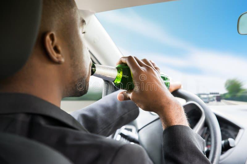 Cerveja bebendo do homem de negócios ao conduzir o carro foto de stock royalty free