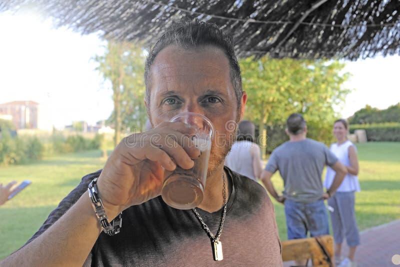 Cerveja bebendo do homem em uma barra exterior No fundo alguns amigos que apreciam Cerveja no vidro pl?stico imagem de stock royalty free