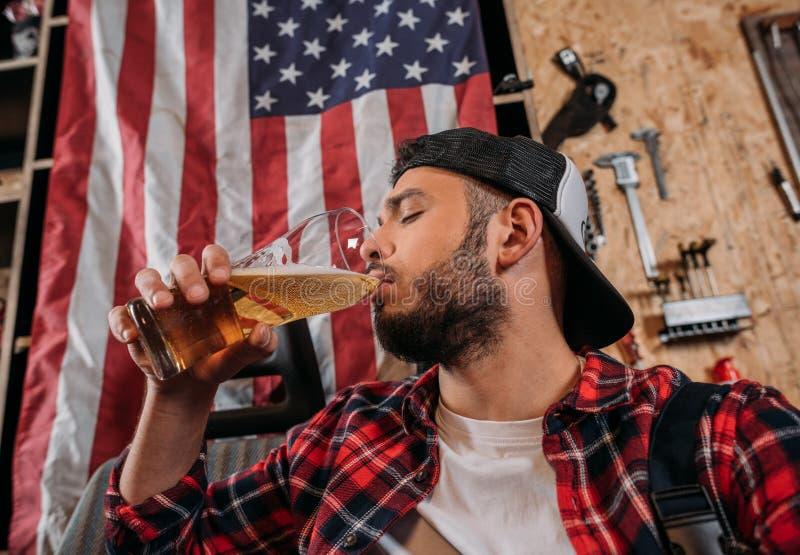 a cerveja bebendo do trabalhador considerável da estação do reparo na garagem com EUA embandeira a suspensão fotografia de stock royalty free
