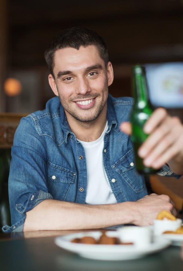 Cerveja bebendo feliz do homem novo na barra ou no bar imagens de stock royalty free