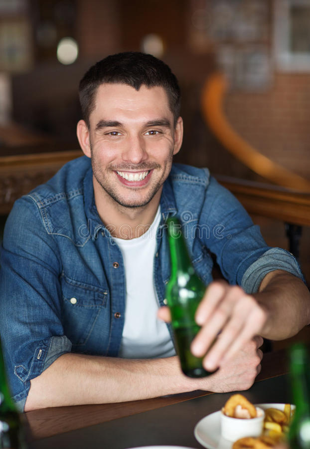 Cerveja bebendo feliz do homem novo na barra ou no bar imagens de stock