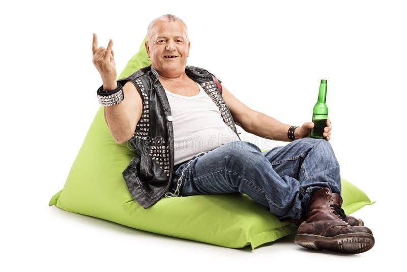 Cerveja bebendo punk madura assentada no beanbag fotografia de stock
