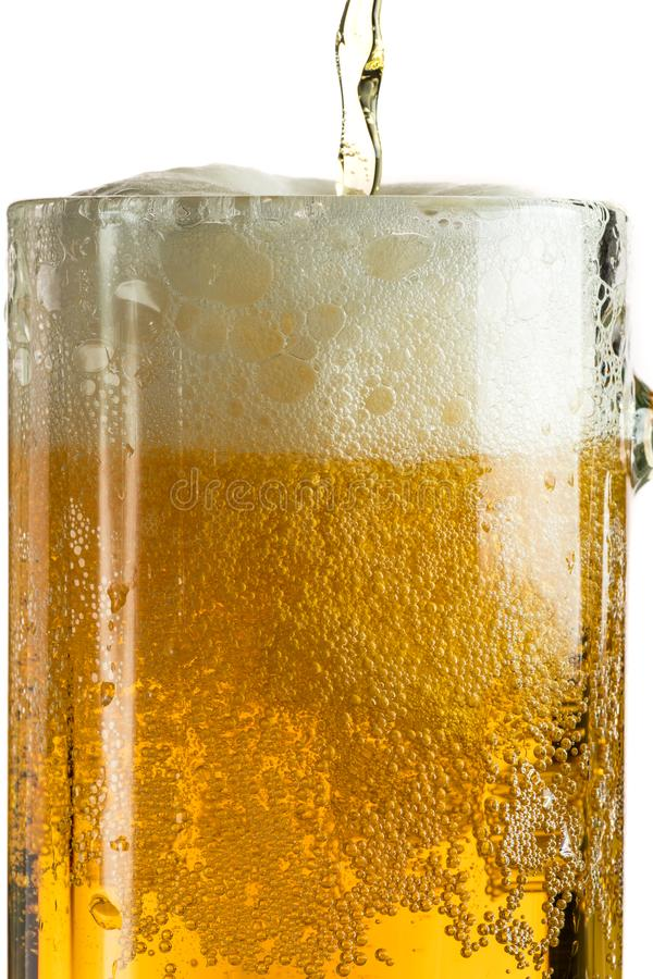 Cerveja clara de derramamento em uma caneca de cerveja, despeja a espuma e o pulverizador imagens de stock
